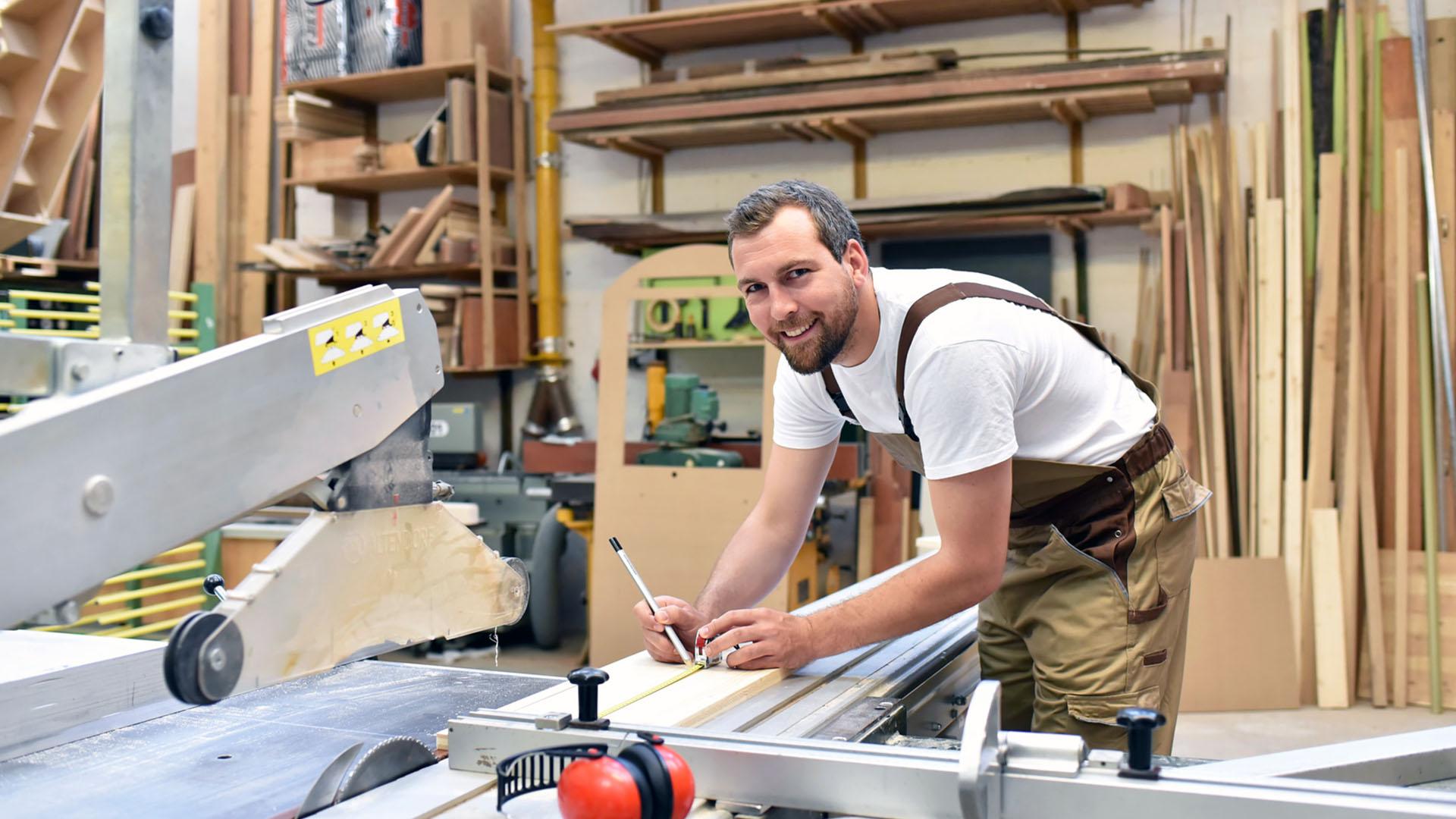 Tischler arbeitet an einer Sge in einer Schreinerei // Carpentry